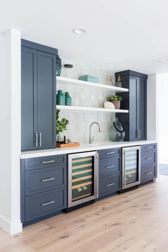 Navy kitchen with turquoise accents. Open shelving, wine fridge. Marble bench top and cool splash back.