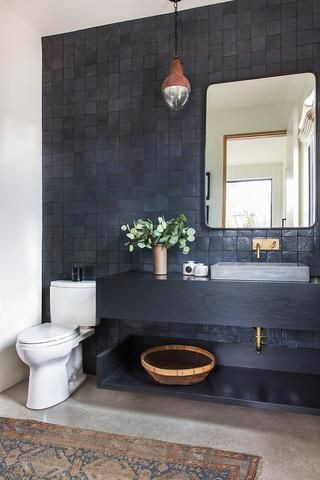 Rough charcoal coloured square tiles behind black wall-hung vanity with exposed brass piping. Cement semi-recessed sink with brass wall mounted tap below square mirror. Single timber and glass light pendant hangs above the vanity to the left. A white toilet sits between the vanity and white wall. On the floor is grey tiles and a vintage Turkish style rug.