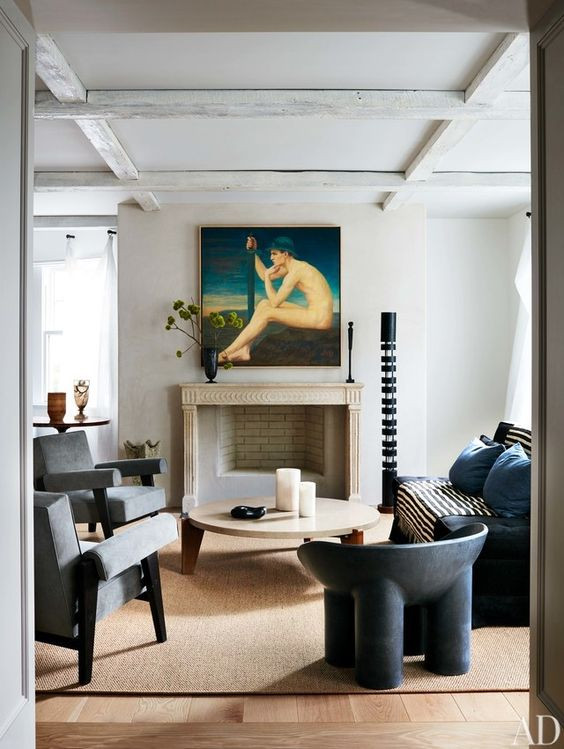 Fine art over fireplace. Pierre Jeanneret arm chairs,  a roly poly chair by Faye Toogood, and a sofa by Christian Liaigre surround a Jean Prouvé cocktail table. Serge Mouille floor lamp; Axel Jarl painting.