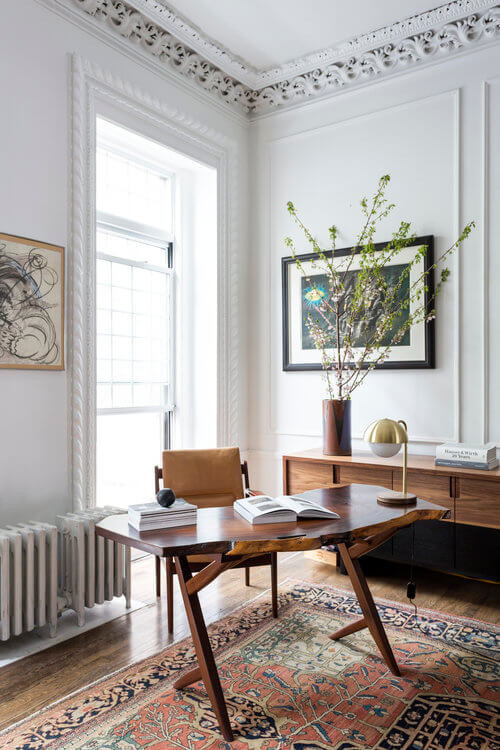 Beautiful home office with mid centruy desk chair, a living edge timber desk with an open book laying on top. Victorian-era crown moulding. Old fashion radiator. Light coming from a window behind the desk. Mid Century storage console to the right. Tree branches in vase. Abstract art on the wall. Bohemian persian rug on golden timber floors.