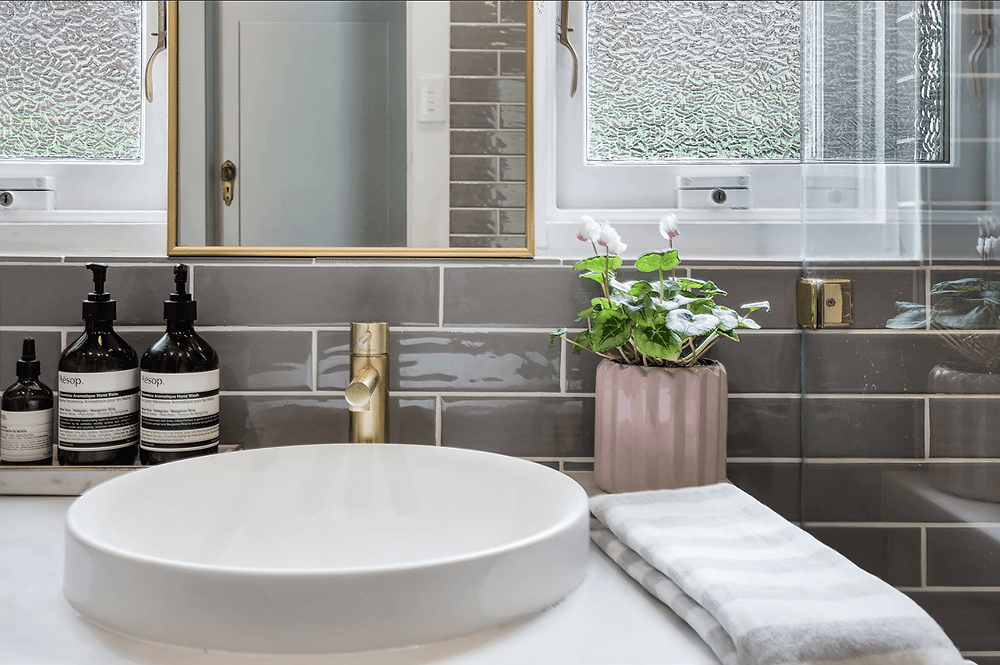 Grey ceramic subway tiles with white grout. A semi recessed round sink with a brass tap and marble vanity and brass mirror. Also on the vanity a flowering plant in a blush pink planter and a grey and white striped Turkish hand towel. A marble tray holds soaps and lotions from Aesop.