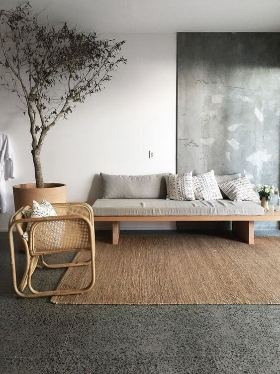 Japandi living room with large muted abstract wall art. Square armless sofa with tribal patterned white throw cushions. A square open bottom cane armchair viewed from the side is in the foreground. In the left corner is a large terracotta potted tree. The room is grounded by a large woven jute rug. The walls are white and squareset.