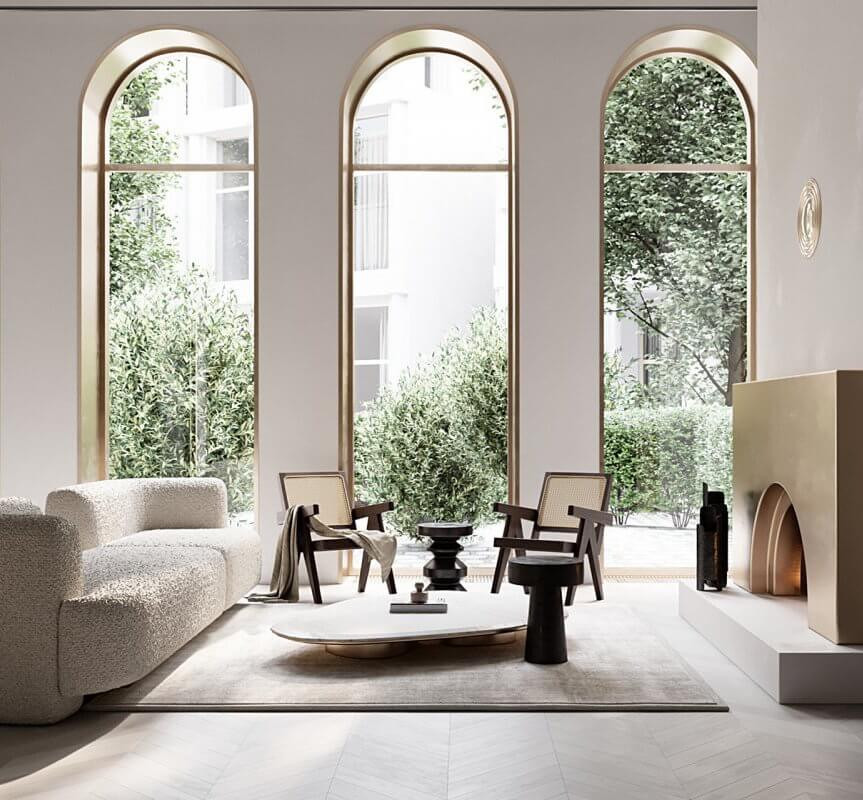 Three tall arched windows complimented by a arched brass fireplace. A modern living room with an arched white sofa and low coffee table place on a rug accompanied by two vintage Pierre Jeanneret timber armchairs. View of olive trees from the large windows.