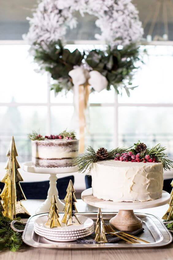 Beautiful lightly frosted cakes sit on multi height pedestals and decorated with pine garland and berries. The table beneath is decorated for Christmas in July with brass Christmas trees and a round flocked wreath hangs in the window above.