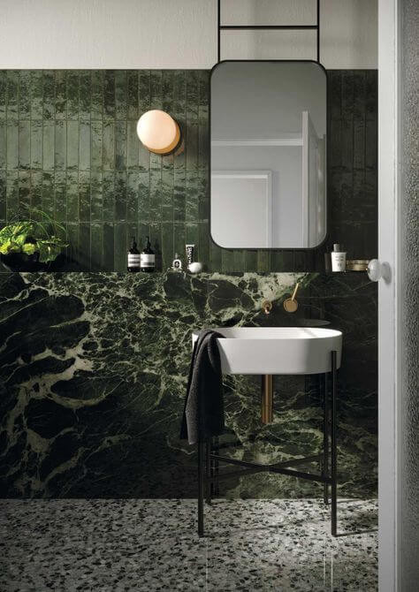 Modern bathroom with forest green vertical stacked subway tiles sitting above a matching built-in green marble shelf that goes to the floor. The white sink is elevated on skinny black metal legs and brass pipes and taps are on display. The floor is a green, grey and white terrazzo tile.