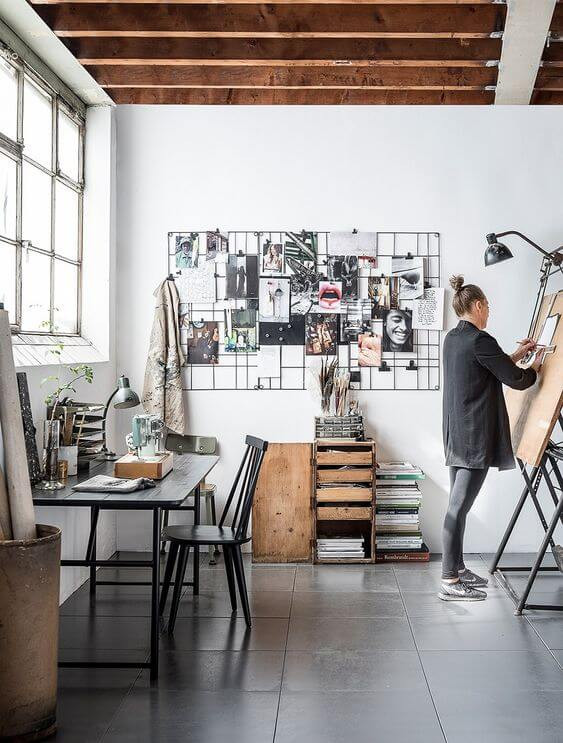 At home art or design studio with late twenties blond woman painting at an easel. Desk is sat against the wall beneath a steel-framed wall. Mood board on adjacent wall to provide inspiration. Dark charcoal tile flooring and exposed ceiling beams.