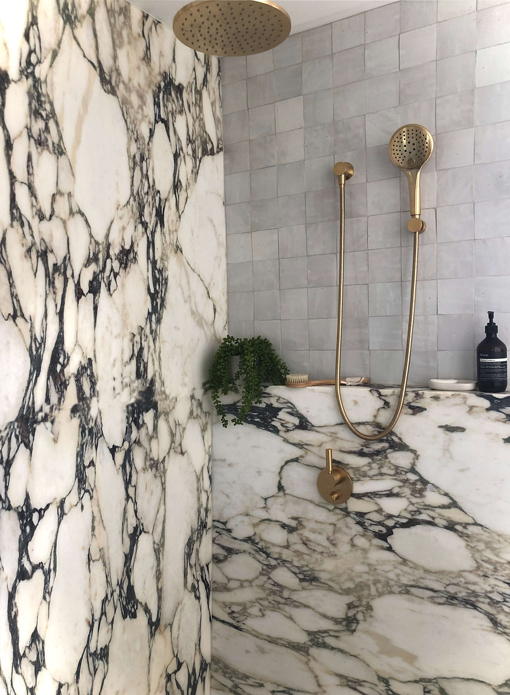 Luxury shower with large calacatta viola Antiqua marble slabs on the wall and creating a bath shelf. On top of the wall is clé ceramic square tiles in a beige colour. Also shown is a brushed brass waterfall shower and a matching handheld shower. Sitting on the shelf is a dangling plant and Aesop shampoo and a cream-coloured soap dish.