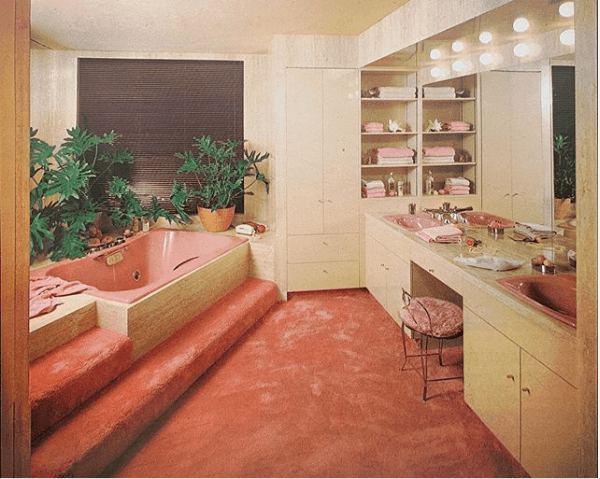Pink wall-to-wall carpeting in a 1980s bathroom. Complete with a step up pink bathtub, light timber built-ins and a pink sink in the glamour vanity with hollywood lights on top of the mirror.