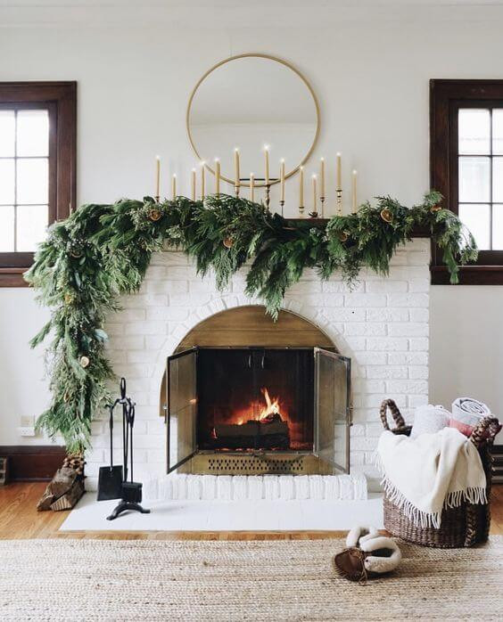 White painted classic brick fireplace decorated with natural pine garland and lit pillar candles with a modern brass round mirror above. Decorated for Christmas in July.