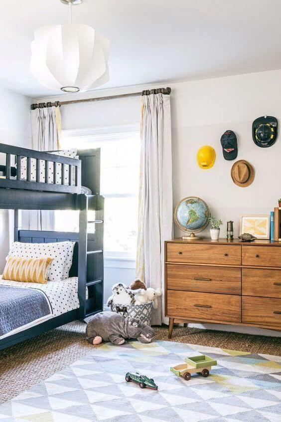 Black bunk beds with grey, white and yellow bedding. Modern boy's room. Collection of hats hanging on the wall as functional decoration, including a hard had and firefighter's hat. White drapes and white paper style pendant. Wall-to-wall carpeting layered with a grey and white diamond rug. Toys on the floor, and a timber mid-century dresser with books and globe on top.