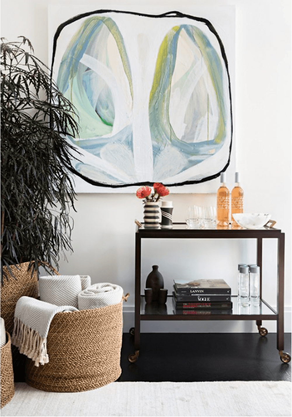 Nate Berkus artwork hanging aboce bar cart with spring flowers and light blankets in baskets.