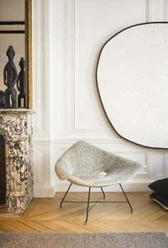 A Parisian style living room with honey coloured parquet flooring, a deeply veined marble fireplace with tribal sculptures and a large brass mirror sit on top. The walls have ornate mouldings and are painted white. A modern grey chair sits alone with an extra large organic round mirror with a black frame hanging on the wall behind.