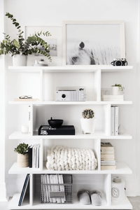 White open shelving with plants, chunky blanket, magazines, art, pottery, and record player.