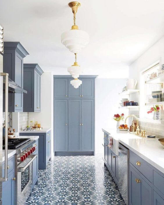 Blue cabinetry in galley kitchen. Shaker doors. Brass pendants and hardware. Spanish style tiles.