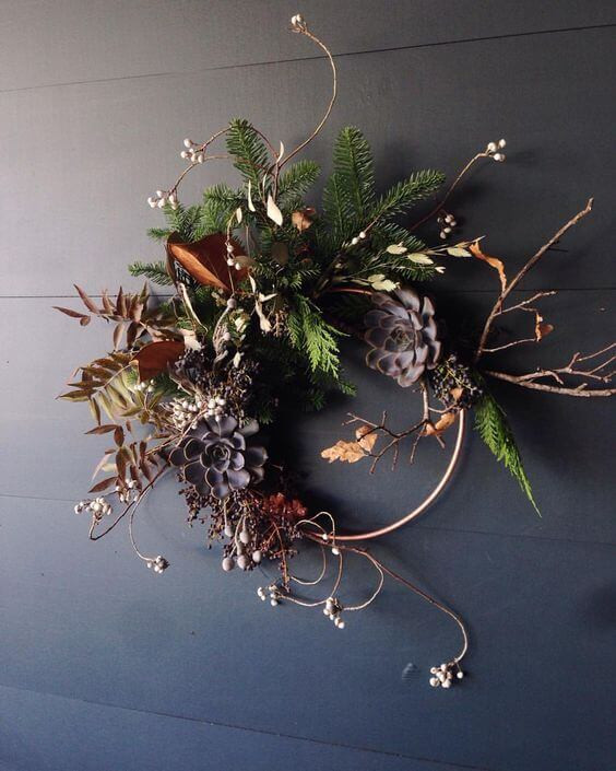 Multi-season wreath with brass ring partially exposed. Wild dried plants emerge from different directions. Christmas in July.
