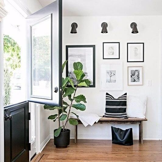 Entrance of a home with a gallery wall and three black sconce lights hanging above a natural timber bench with cushions and throw blanket on top. The floor is oak and a large bag sits below the bench. To the left sits a fiddle leaf potted plant. The walls are white, and the door is black, with the top half swung open, letting in fresh air.