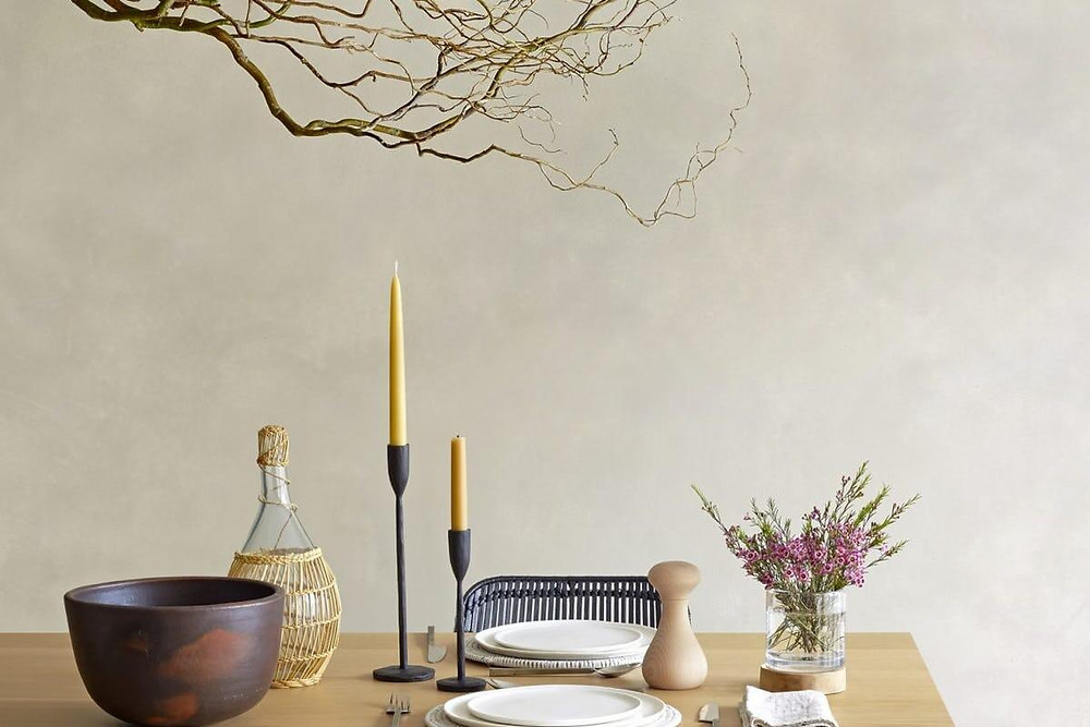 Japandi table set with wicker and glass water jug, light and dark timber accessories, small purple flowers. An organic branch hangs above black candle holders with light mustard-coloured tapered candles. White dishes at place setting. Black woven chair and blond timber dining table.