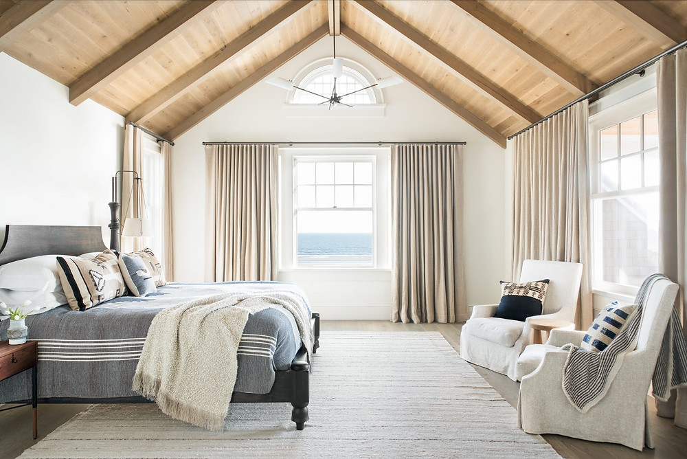 Spacious bright and airy Modern Farmhouse Master Bedroom. Tiber Vaulted Ceilings. Timber Floors. Modern Pendant. Traditional Chairs. View of Atlantic Ocean.Beige Drapes.