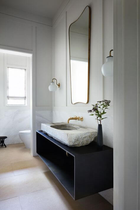 A white timber panelled bathroom. Wall hung black vanity with an open shelf and a rough-cut stone sink sat on top. A wall mounted brass tap sits below a curved brass mirror. The brass mirror is flanked by two traditional glass globe sconces. On the floor is wide plank timber.