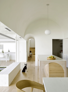 A modern home incorporating 2020 interior design trend of arches. White walls and timber floors and furnishings. Cute French Bulldog and child. Kitchen and Pantry with open plan living.