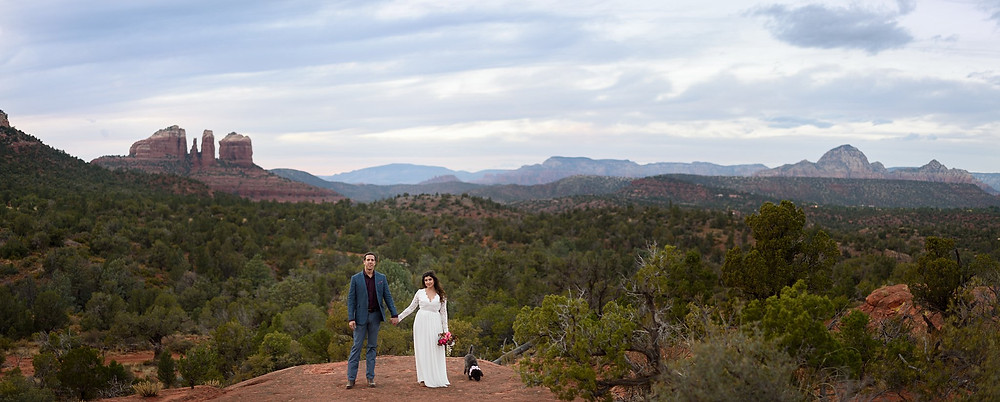 Panoramic photo of a newly married couple standing on the top of bell rock