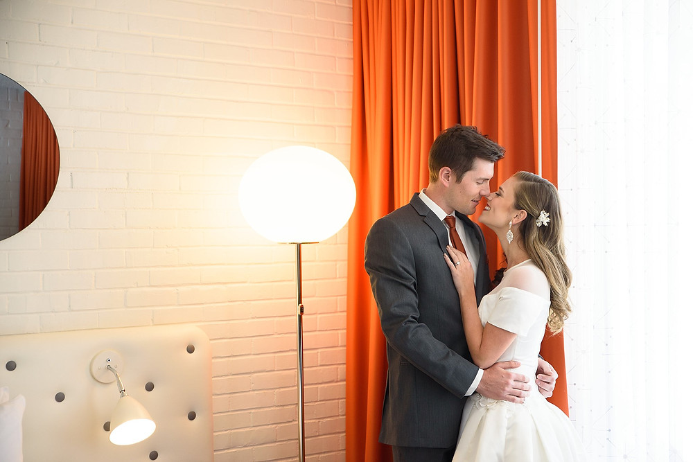 bride and groom touching noses and smiling in hotel valley ho suite