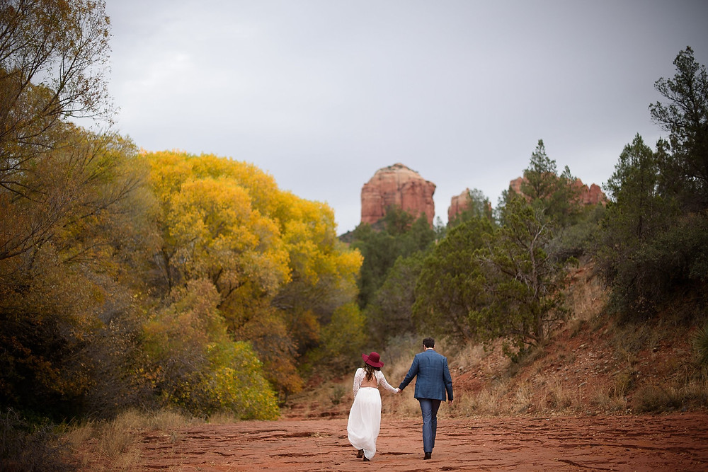 Couple in Sedona walking together on a hiking trail holding hands