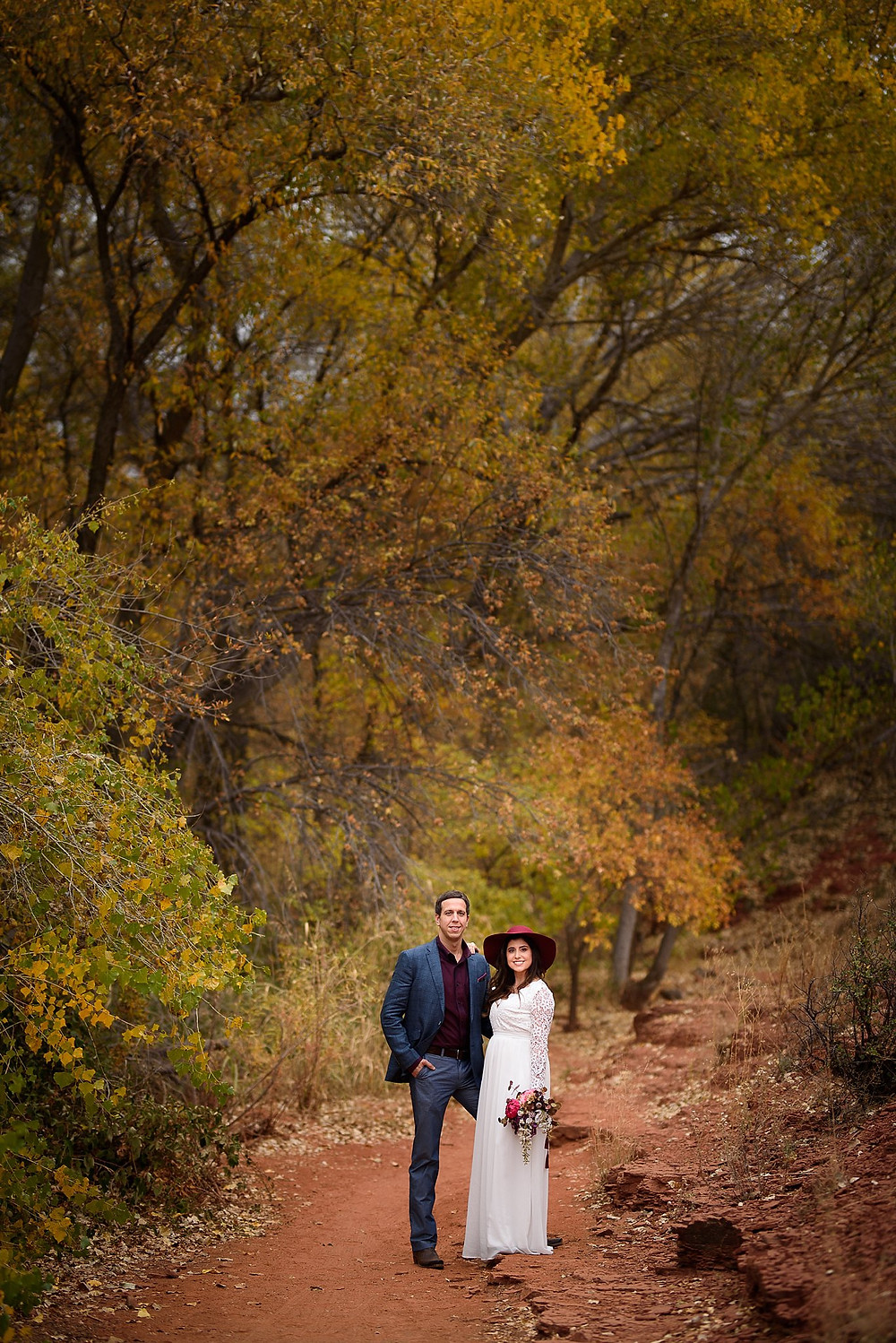 Couple in Sedona posing on a hiking trail for photos