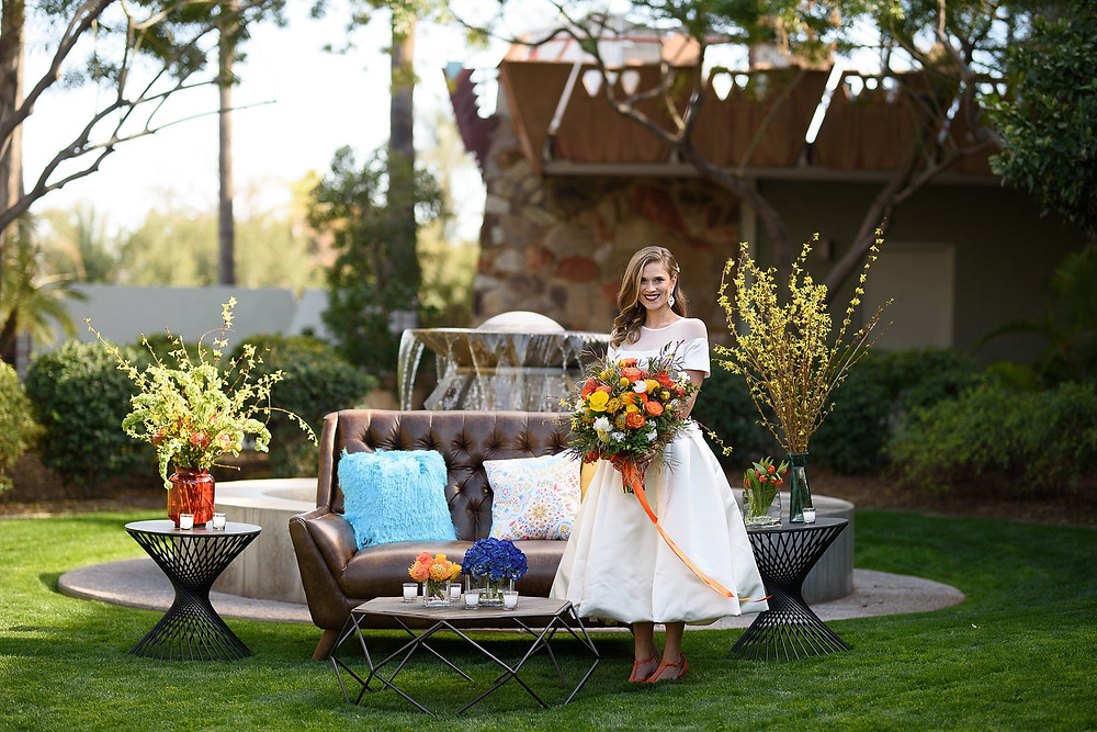 bride standing outdoors next to a couch and table holding her bouquet