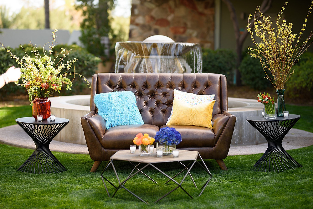 outdoor seating area with a brown leather couch and tables with flowers