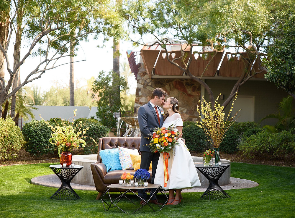 bride and groom standing outdoors next to a couch and table bride holding her bouquet