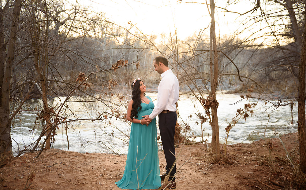 pregnant mother and father standing near oak creek holding moms belly smiling at each other