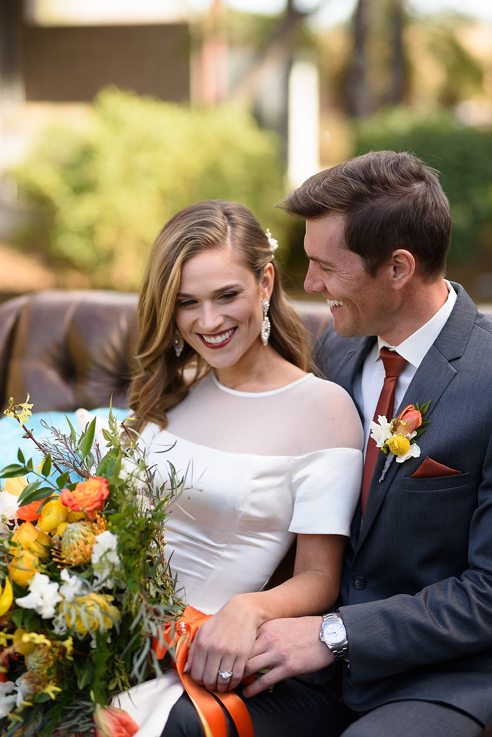 Bride and groom sitting outside on a brown leather couch while laughing