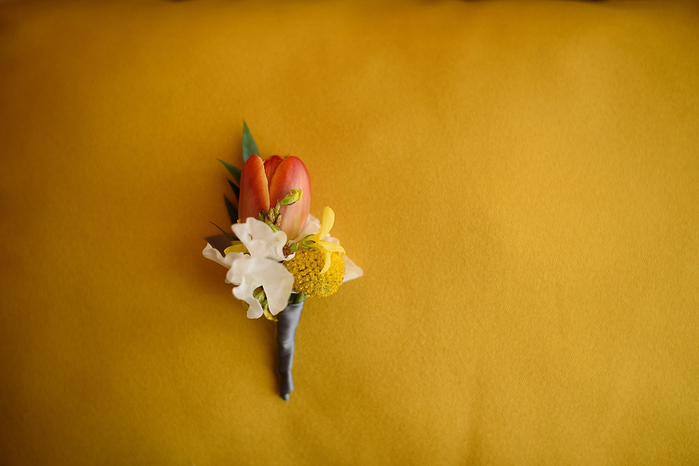 grooms flower boutonniere on bright yellow background