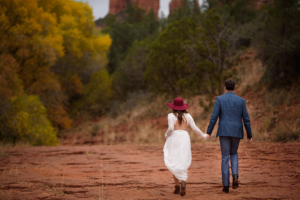 Couple in Sedona walking down a hiking trail holding hands