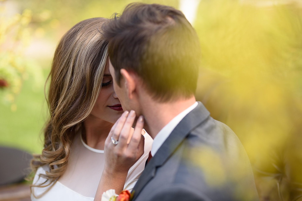bride and groom touching foreheads together while bride touches grooms face