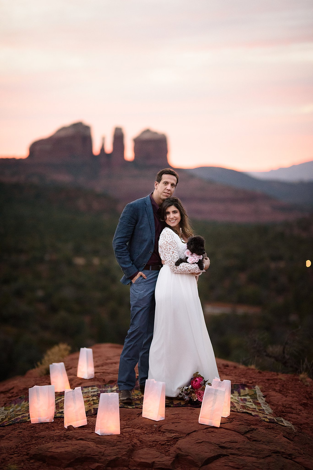 Newly married couple in Sedona posing for a photo with their puppy with Cathedral Rock in the background