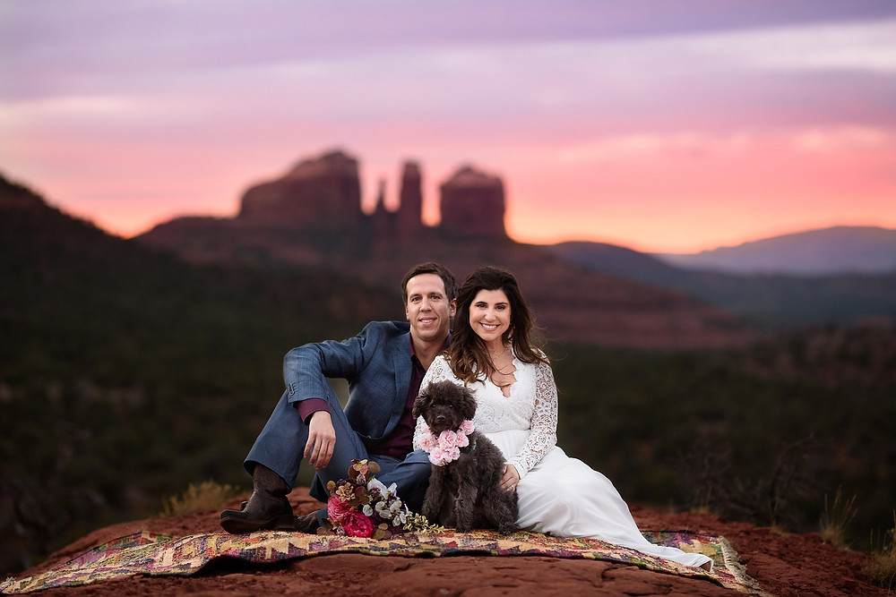 Newly married couple on the top of baby bell rock in Sedona at sunset with Cathedral Rock in the Background