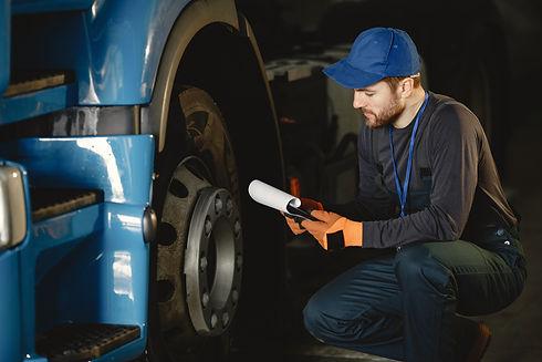 young-worker-checks-wheel-truck-malfunct