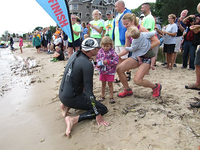 Family warmly greets swimmer at Mighty Mac Swim finish