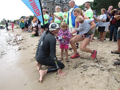 Family warmly greets swimmer at Mighty Mac Swim finish