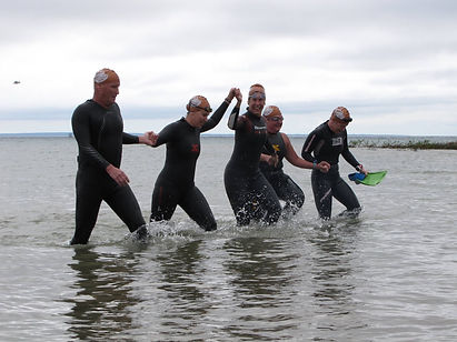 Swimmers joyously finishing together in the Mighty Mac Swim