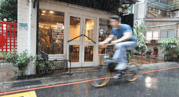 Adult man riding an electric bike in rain.png