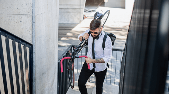 adult man carrying electric bike up stairs