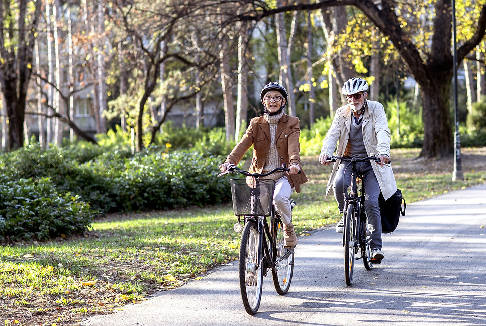 Older couple cycling on electric bikes in a city park