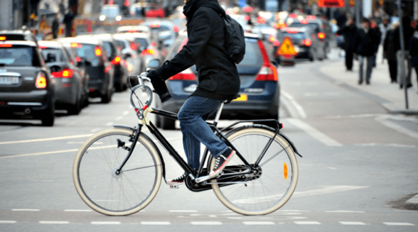 Adult man commuting on an electric bike in city traffic