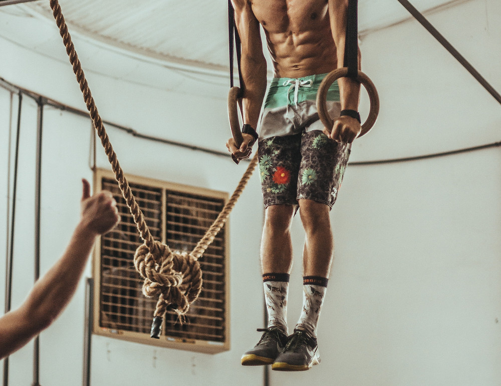 man on olympic rings with 6 pack abs