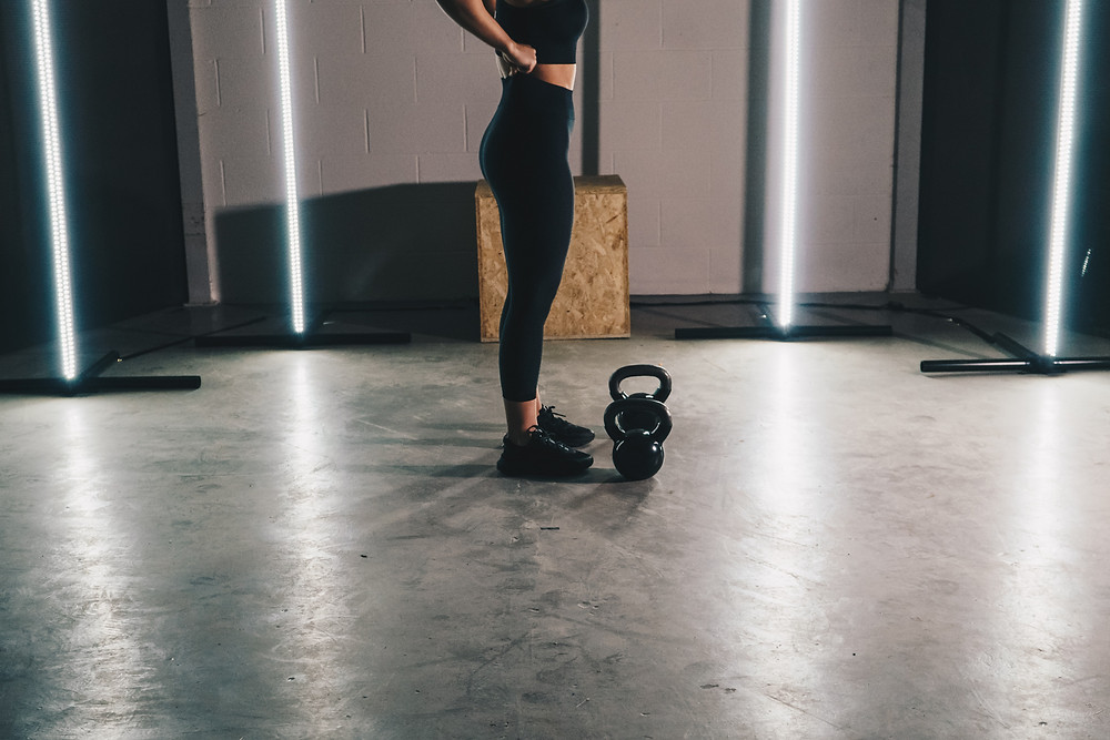 woman in black leggings in a gym with a kettlebell