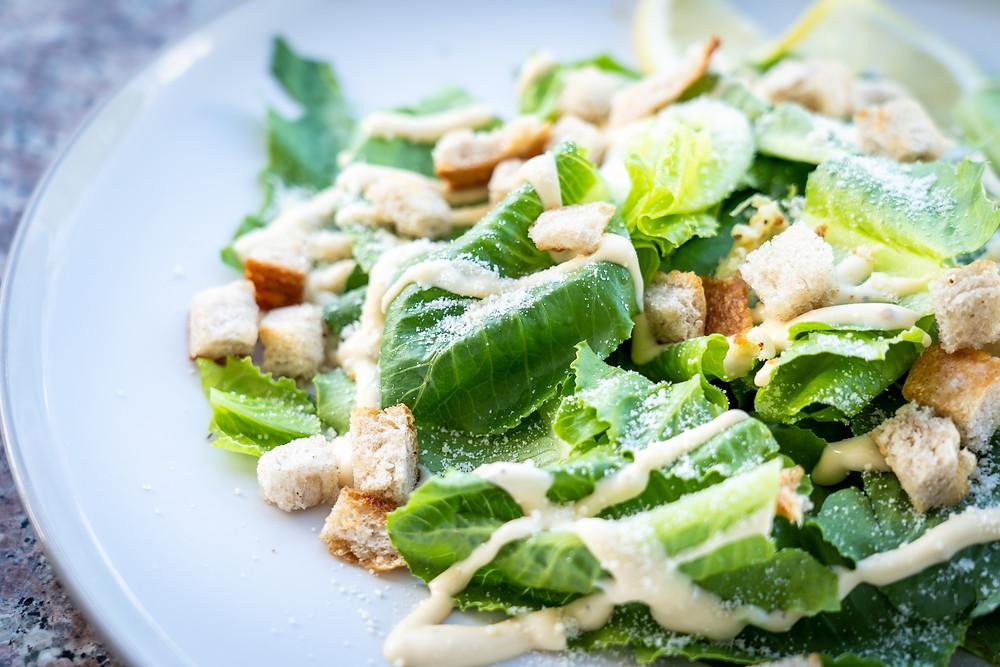 a ceasar salad on a marble table