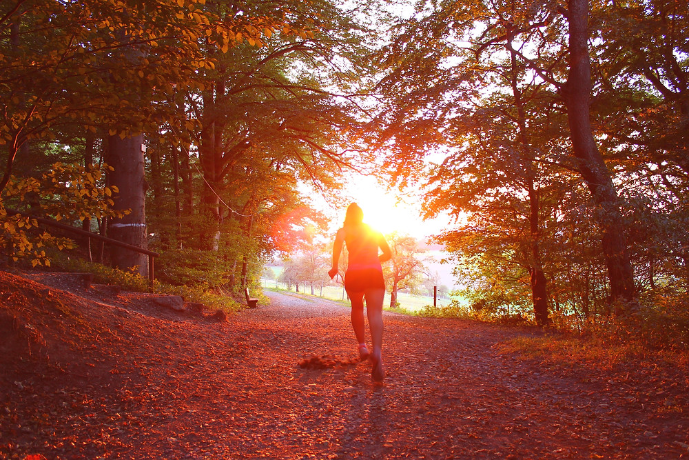 lady running in woods in autumn
